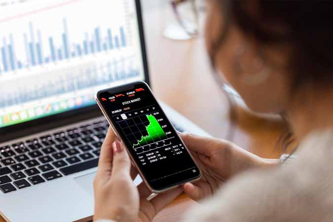 A person checking stock charts on a smartphone and a laptop.