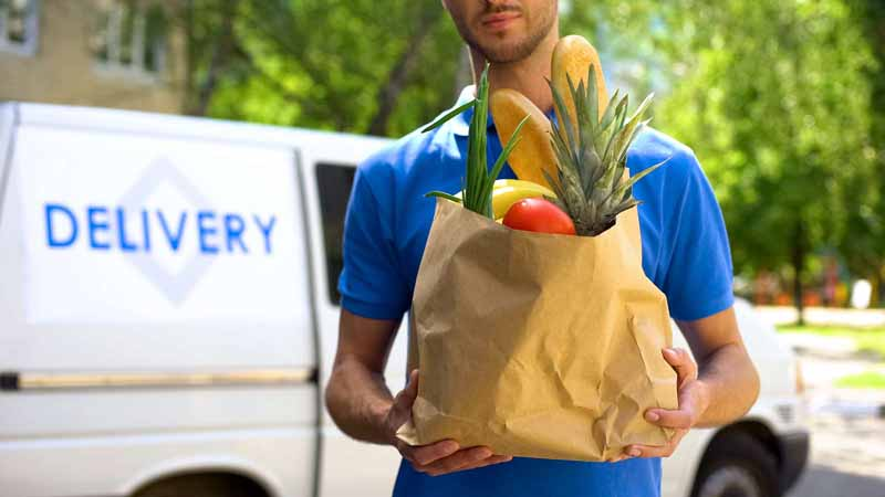 Grocery delivery person holding a bag of groceries.