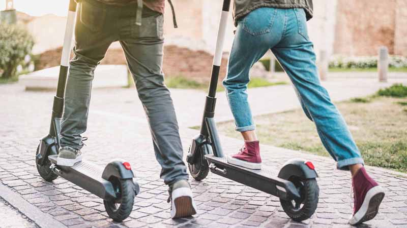 Two people using electric scooters in a park.