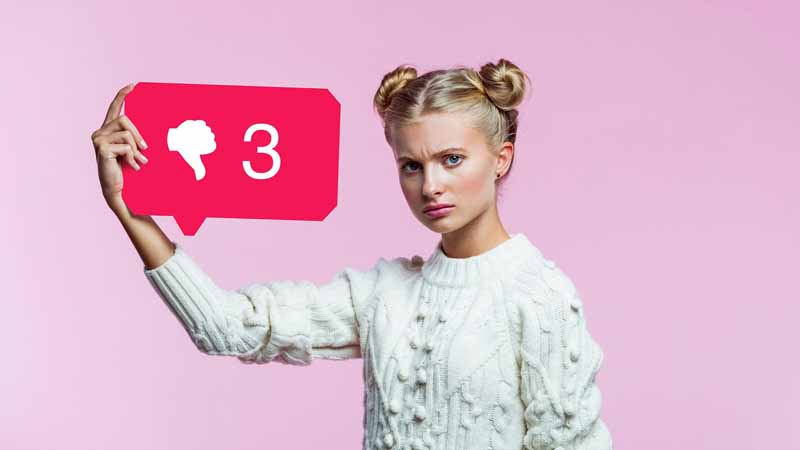 A girl holding a speech bubble with three social media thumbs down.
