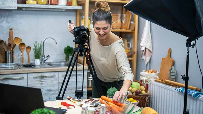 A woman in her kitchen creating a food vlog.