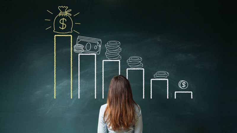 A woman standing in front of a chalkboard with a financial bar graph.