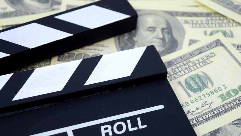 A clapboard on a pile of money.
