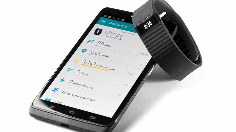 FitBit Charge device next to the FitBit app.