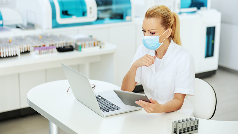 A lab assistant wearing a face mask working on her computer.