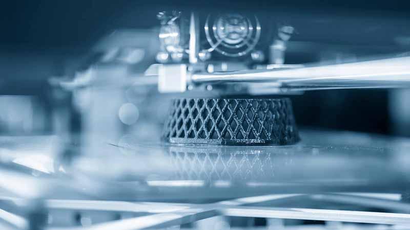 Close-up scene of 3D model printer operation.