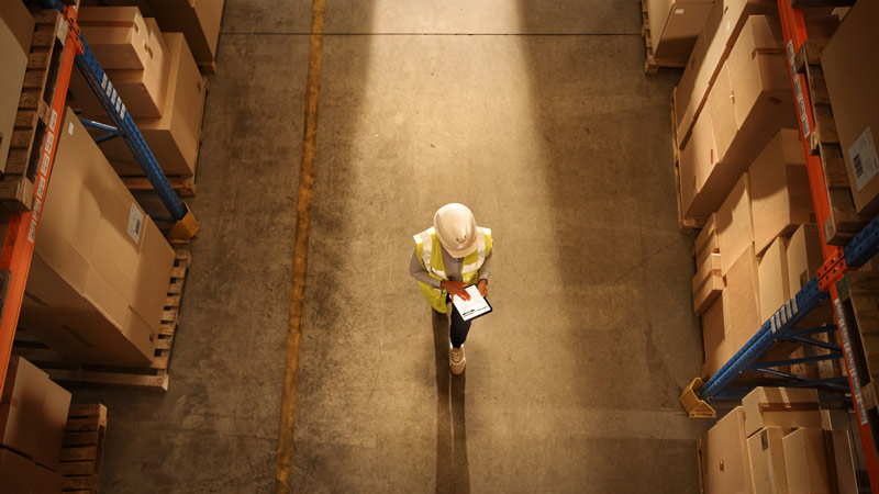 A worker in a hard hat checking warehouse inventory.