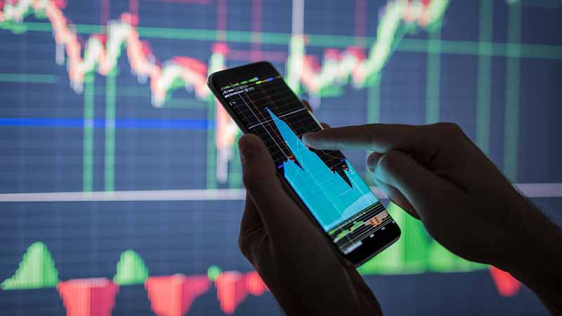 Businessman checking a stock market app on a smartphone.