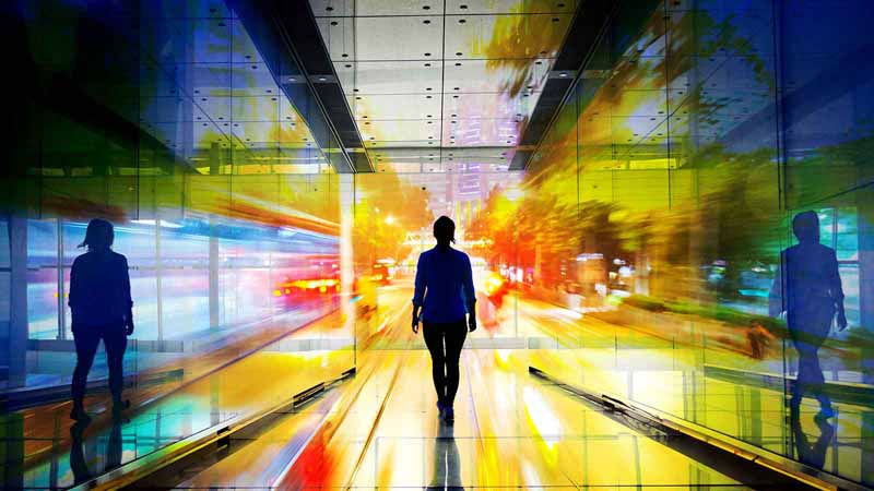 Double exposure of a businesswoman walking down a hallway.
