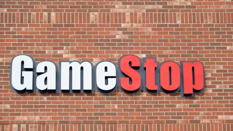 A GameStop sign on a brick building.