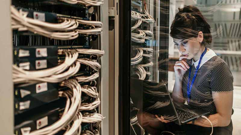 A woman working in a server room.