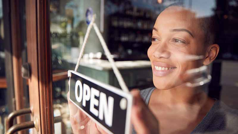 A business owner putting up 'open' sign on her store door.