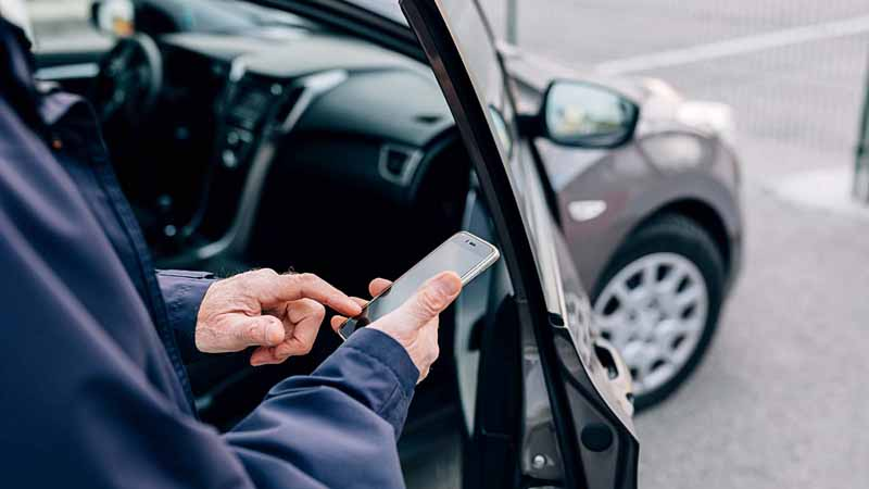 Man using cellphone to rent a car.
