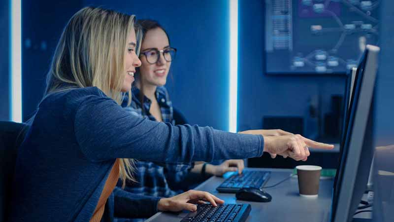 Two female programmers working at desktop computers.