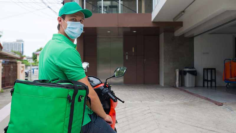 A delivery driver wearing a surgical mask on a motorcycle.