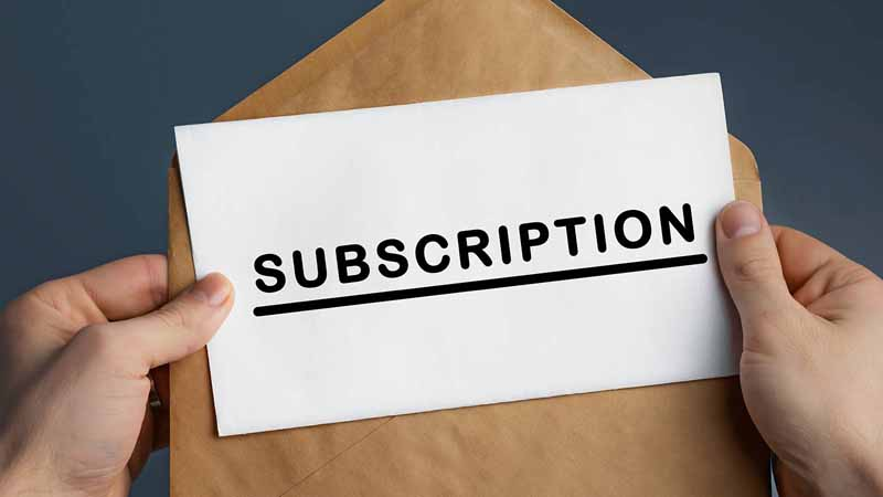 Person holding an envelope and paper that says SUBSCRIPTION.