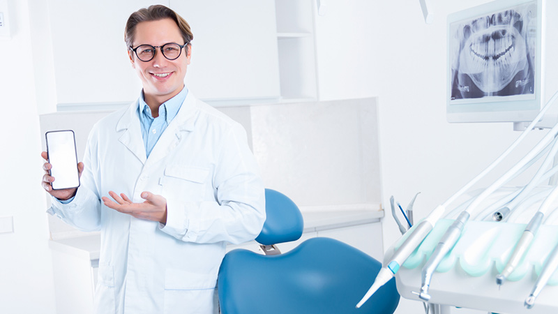 A dentist holding a smartphone in a dental office.