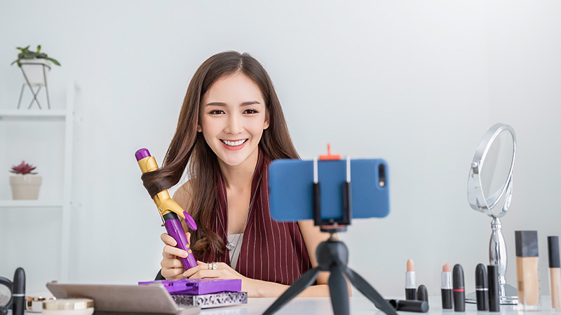 Woman recording video of curling her hair.