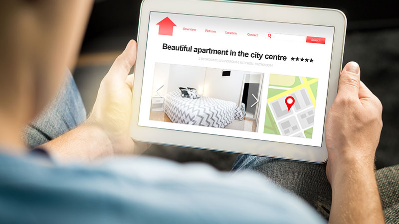 A man searching for apartments on a tablet.