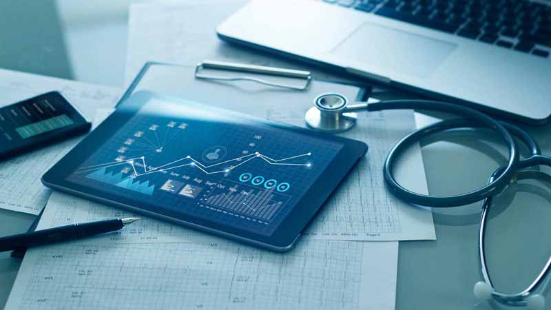 A desk with a stethoscope, medical charts, a laptop, and a tablet.