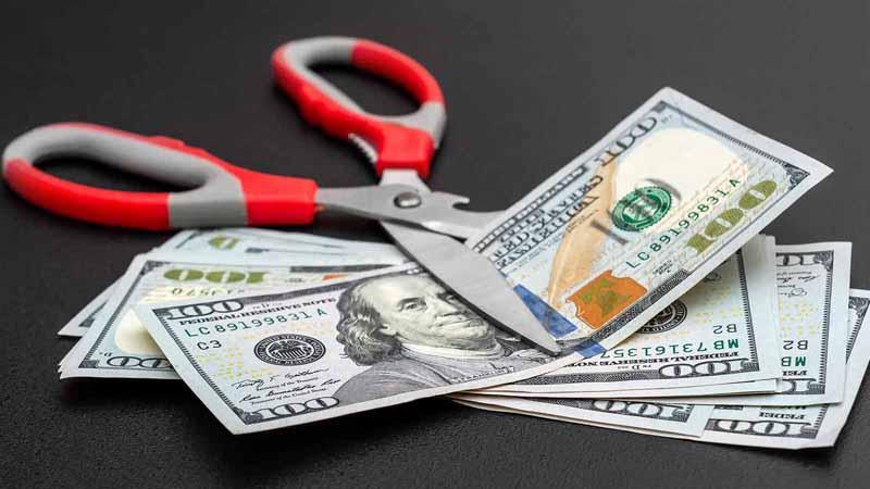 Scissors cutting money on black background.