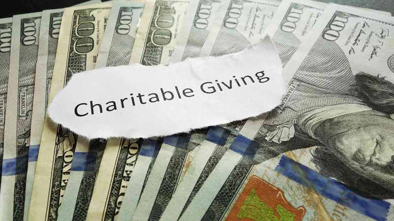 """Stack of dollar bills and paper scrap that says """"Charitable Giving."""""""