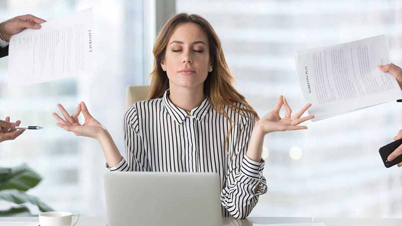 Businesswoman meditating while people hand her forms.