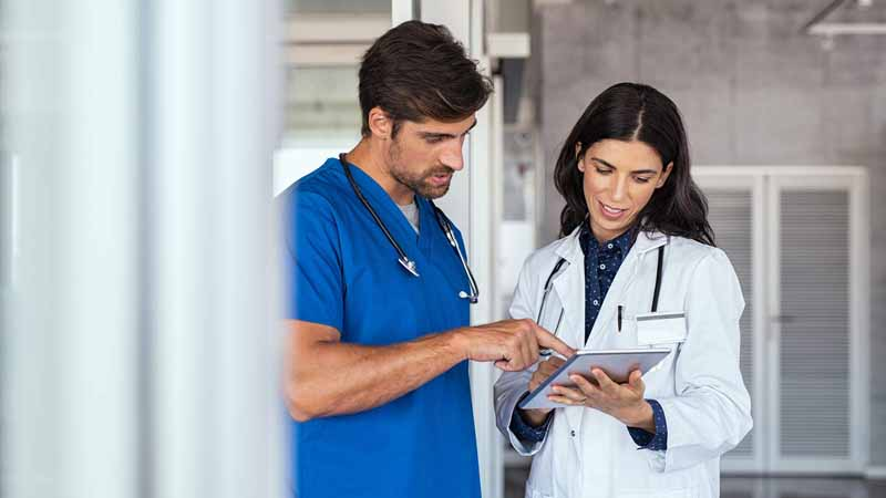 A doctor and a nurse discussing reports.