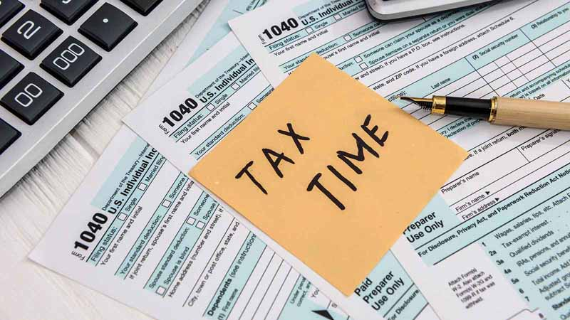 """Pile of tax forms with sticky note that says """"Tax Time."""""""