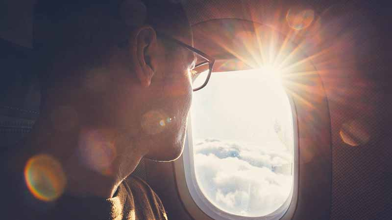 Man looking out the window of an airplane.