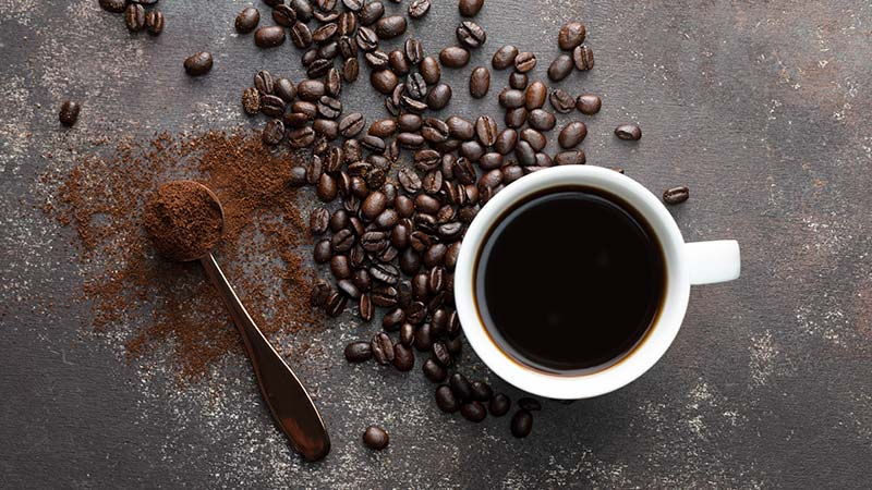 A coffee cup, coffee beans, and coffee grounds.
