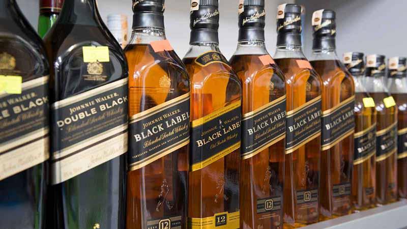 A shelf of Johnnie Walker whiskey bottles.