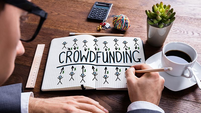 Businessman drawing 'crowdfunding' concept in a notebook.