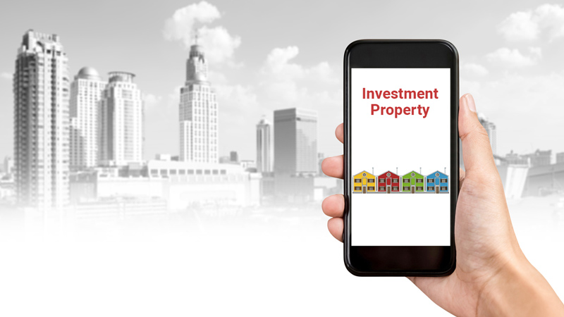 Person holding phone that says investment property with an image of houses below.