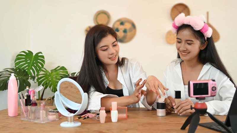 Two teen vloggers creating a makeup video.
