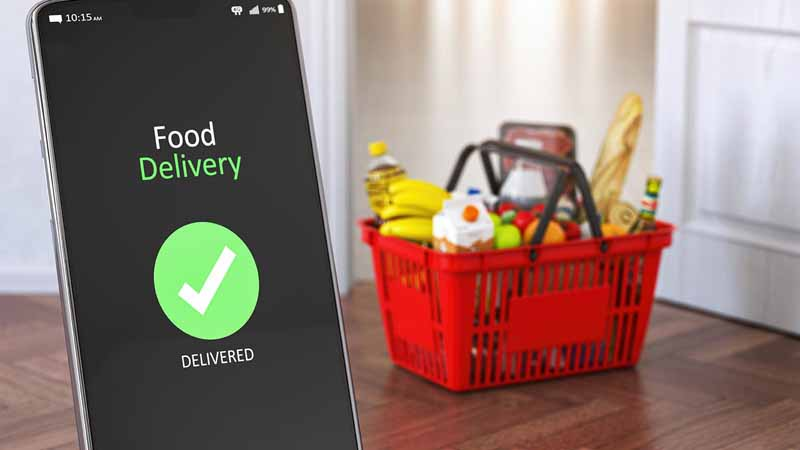 A smartphone and grocery delivery basket in a living room.