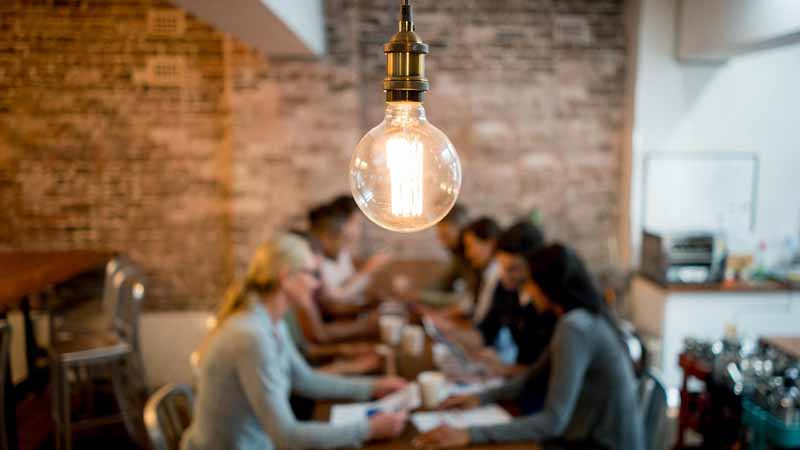 Light bulb and group of business people brainstorming at an office.