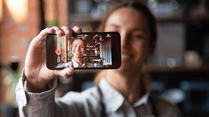 A woman recording a video of herself on a smartphone.