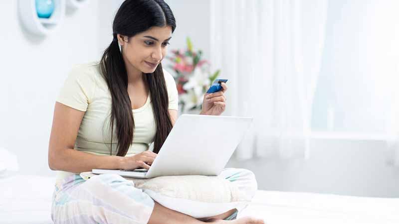 A girl using her laptop in her bedroom.