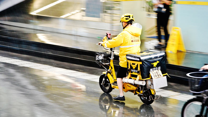 A Meituan delivery courier on a motorbike.