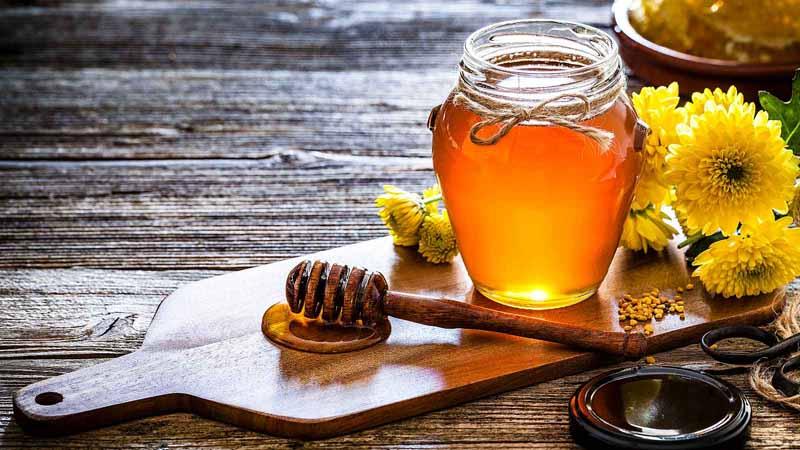 A honey jar with dipper on a cutting board.