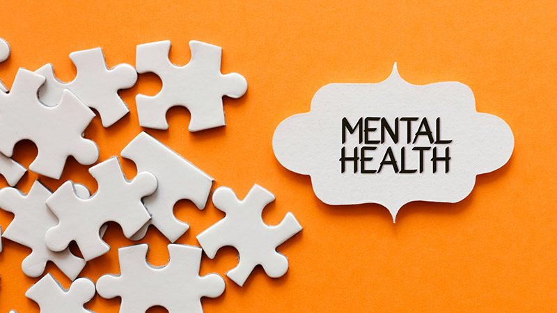 """""""Mental health"""" puzzle pieces on an orange background."""