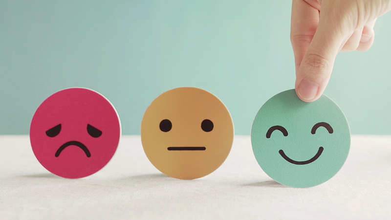 A red sad face, a yellow neutral face, and a green happy face.