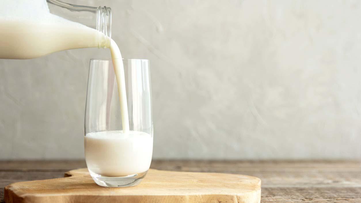 A jug of milk filling a glass.
