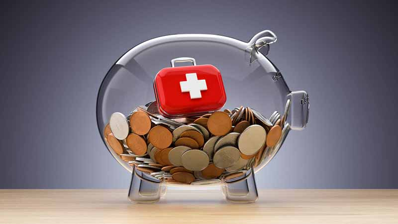 A piggy bank filled with coins and a first-aid kit on top.