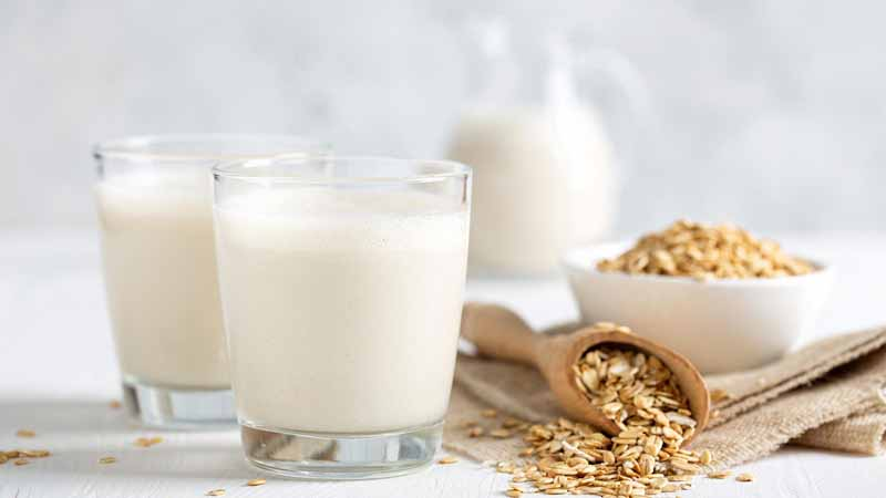 Glasses of oat milk next to a bowl of oats.