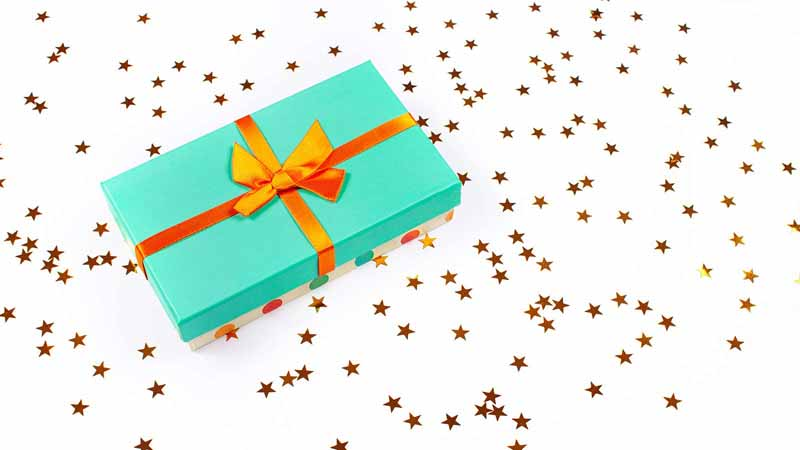A gift box on top of a star-filled surface.