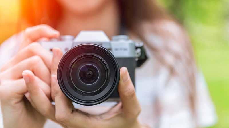 Closeup of a woman holding a camera.