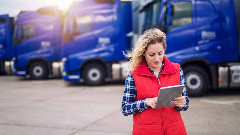 Truck driver reading a tablet.