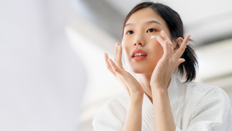 A woman putting moisturizer on her face.
